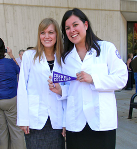 Kirsten Gierach '10 (left) and See-yin So '10 hold up a Purple Pennant after donning their white coats for the first time in a ceremony at Des Moines University's medical school. So came to Cornell because of the Dimensions progtam and is studying to become a physician. (Photo by See-yin So '10)