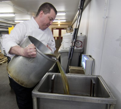 Dan Watrin, executive chef at Bon Appétit on Cornell's campus, pours oil that will be used to make biodiesel.