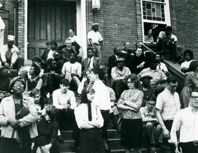 Civil rights activists assemble on the stairs of the Dexter Avenue King Memorial Baptist Church, Montgomery, Ala., where the Montgomery Bus Boycott was organized in 1955-1956. John Watson '68 is at center. Roger Davis '65