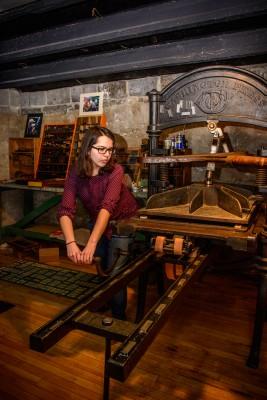 Cornell College  junior Laura Michelson using the college's 19th-century Washington letterpress.