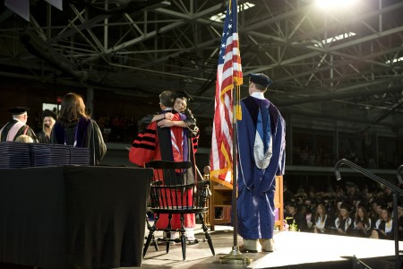 The culmination of four years arrives as Kelly Oeltjenbruns embraces President Jonathan Brand and receives her degree.