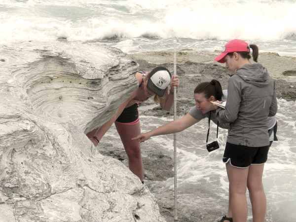 India Pearce '15, Nicole Werling '15, and Hannah Garvey '15 measure a vertical section of rock while studying Pleistocene (fossil) sand dunes in the Bahamas. Photo by Ben Greenstein