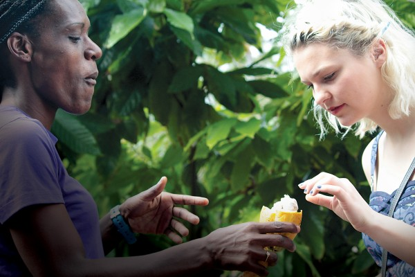 Marie-France Degras (left) and French student Maren Elnes '15 sample cacao from a tree outside the sugar cane museum in Martinique.  Photo by Devan Baty