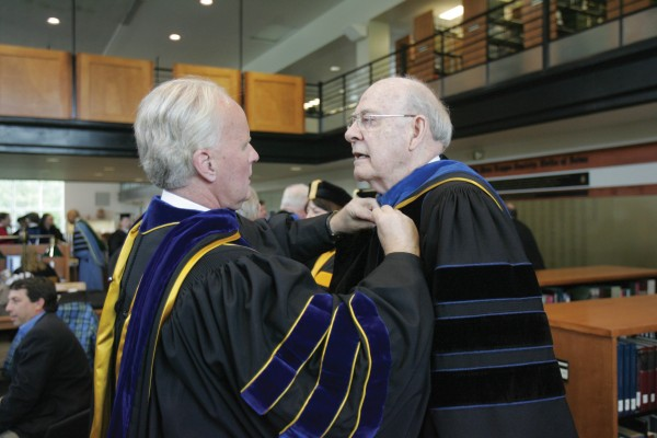 Life Trustee bob Engel '55 receives help with his regalia from a former student, Bob Duffett, president of Dakota Wesleyan College.