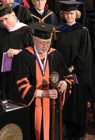 Politics Professor Craig Allin, serving as College Marshal, places the new college mace in its stnd as the ceremony begins. The mace was commissioned in honor of the Brand inauguration by honorary alumna Dyan Smith, wife of John Smith '71, Trustee and chair of the Presidential Search Committee. It was handcrafted by Don Stumbo, spouse of Janene Panfil '89. Once a weapon in medieval England, maces are used today as a symbol of office.