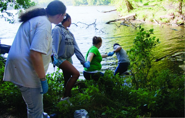 Students reach out to pull an old tire out of Lake MacBride during New Student Orientation Service Day in 2010 (Photo by Jamie Kelly)