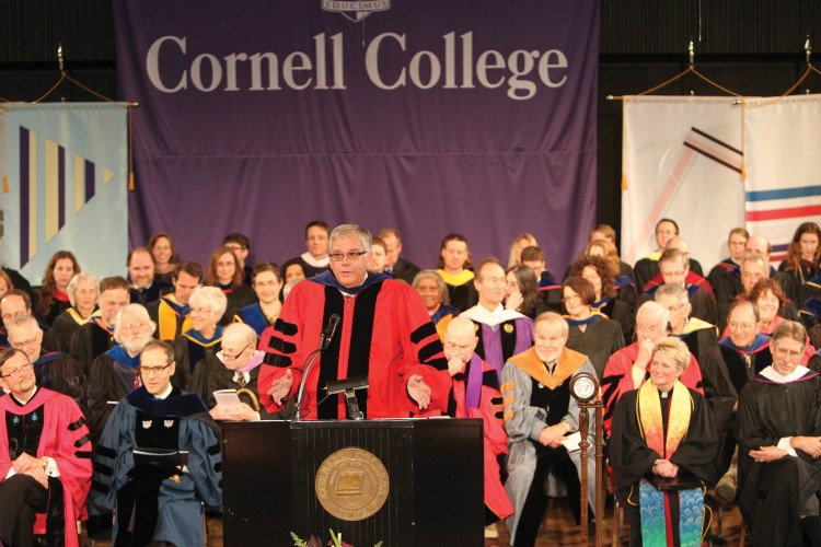 With the faculty seated on stage behind them, John Smith '71 introduces President Brand.