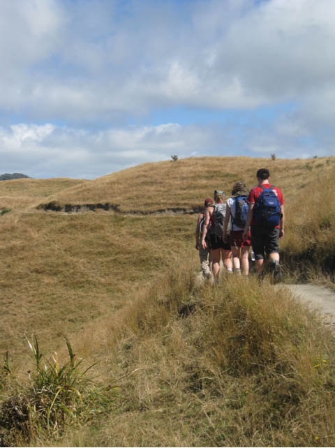 Geology students set off toward Wharariki Beach on the South Island, New Zealand, to examine the cross section of exposed rock cliffs on the beach.