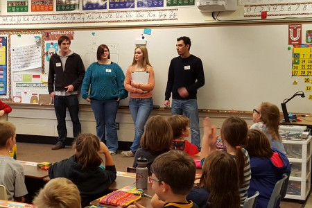Joe Keller '19, Cody-Lee Bankson '18, Sami Vetter '19, and Chris Baluja '19 speaking to a third-grade class at Mount Vernon Elementary.