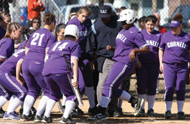 The Rams gather around sophomore Simone Wright as she crosses the plate on a home run against the University of Dubuque.