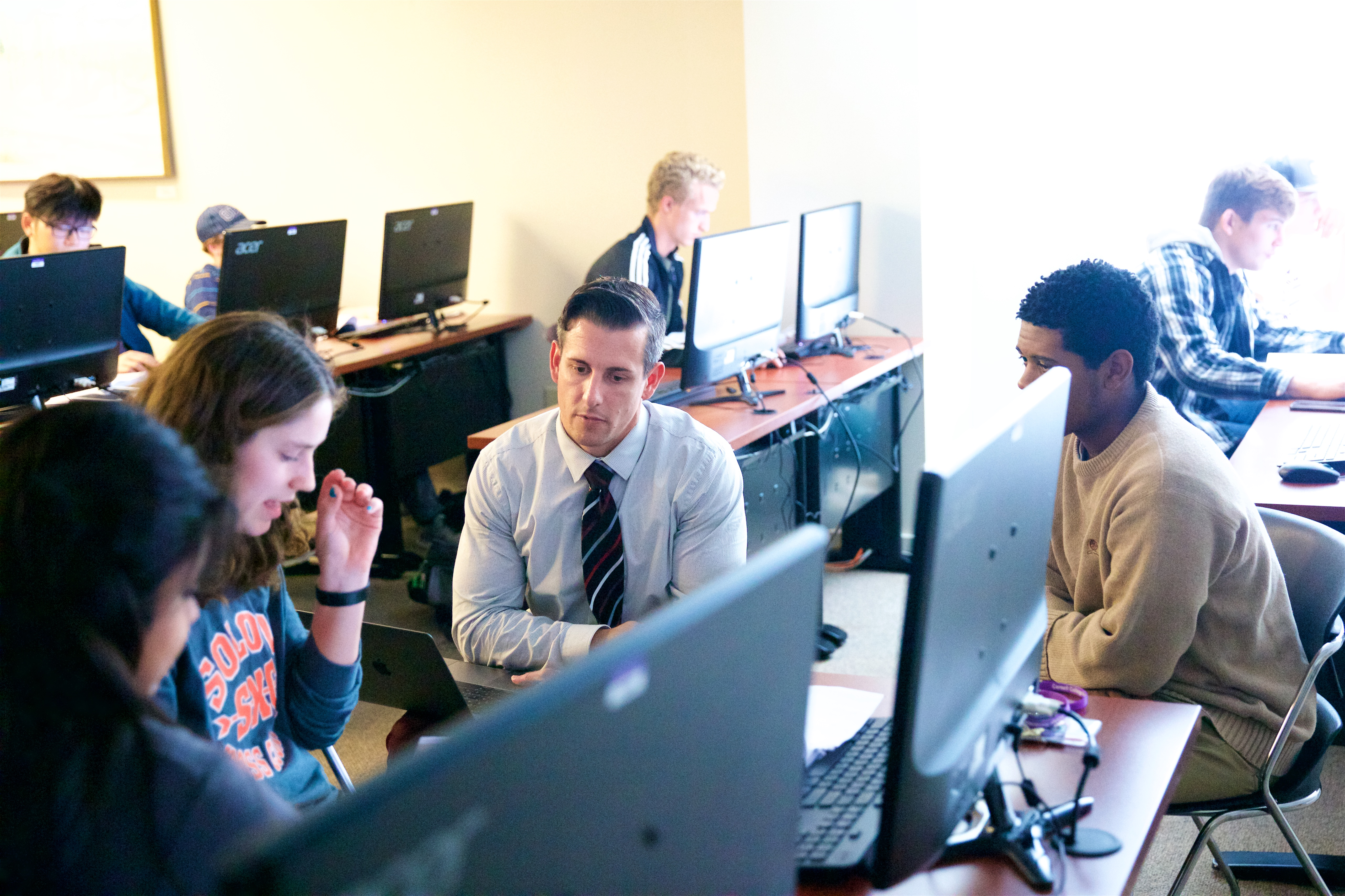 Professor of Engineering Brian Johns (center) consults with a student team designing a new type of dustpan. (Photo by Allan Recalde)