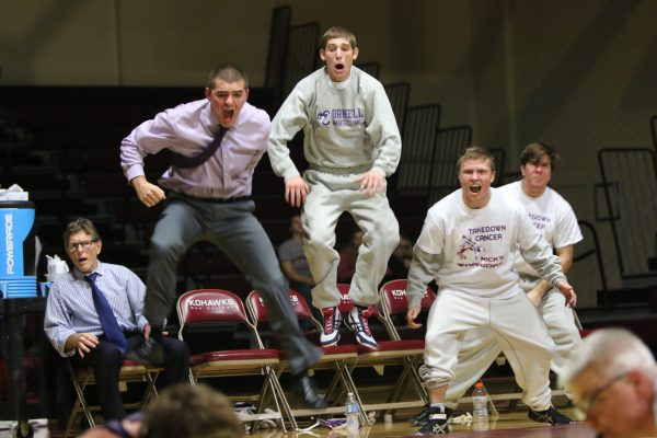 Wrestlers and coaches react to a victory over Coe