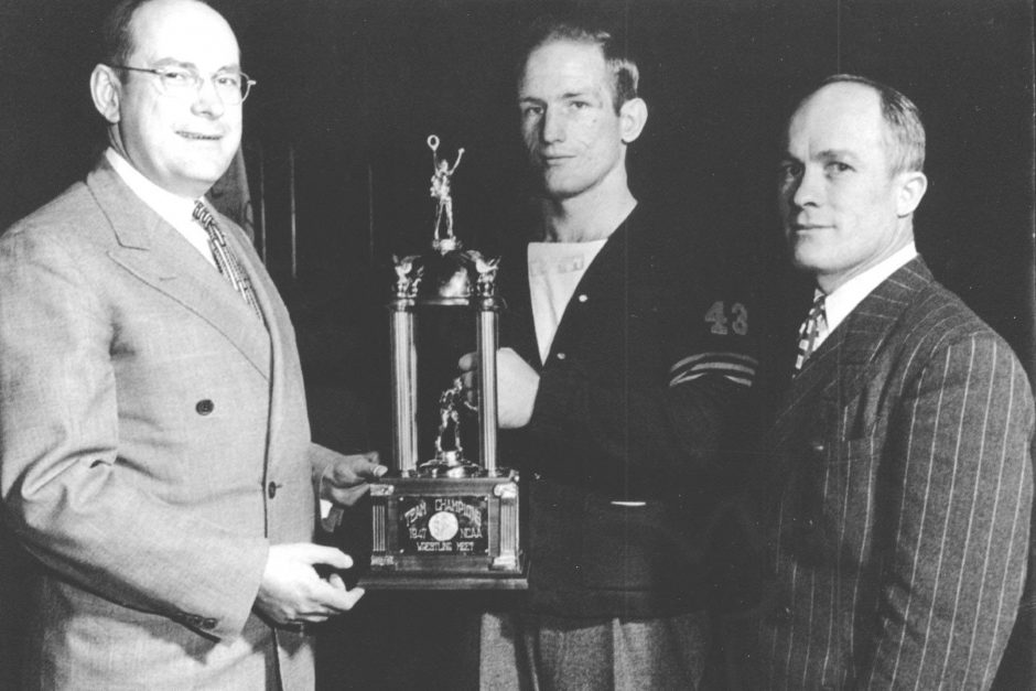 """Cornell President Russell D. Cole, wrestler Dale """"Whitey"""" Thomas and Coach Paul Scott with the 1947 NCAA championship trophy."""