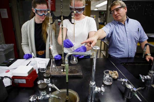 Two students and a professor work on a lab experiment