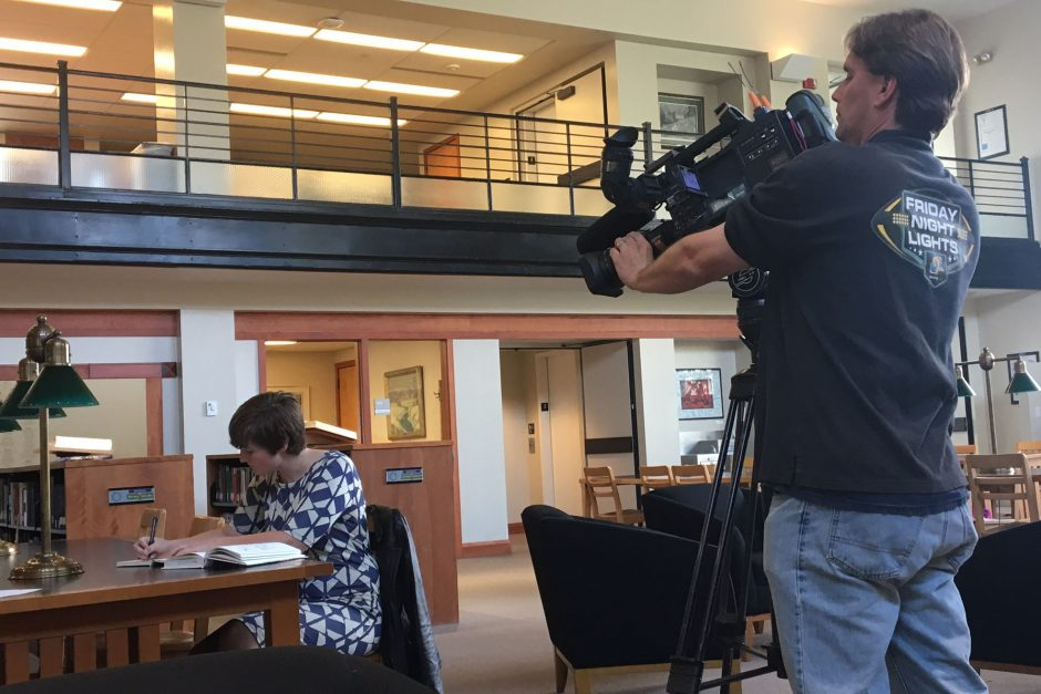 Photographer takes video of student for news story