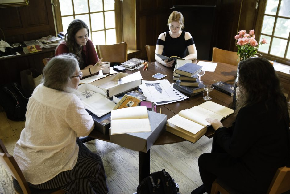 Three students work with Professor Leslie Hankins