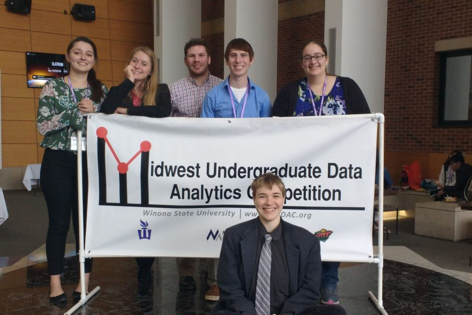 Cornell students posing by sign at a data analytics competition