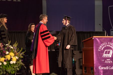 Mackenzie Crow '18 with President Jonathan Brand. They are on the stage shaking hands during graduation.