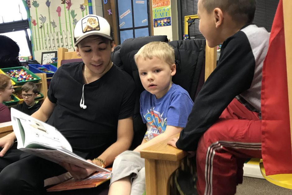 Soccer player Enzo Vanzillotta reads to children