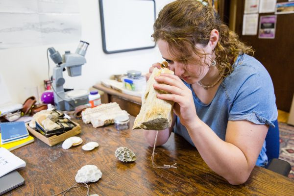 Kira Fish looks at coral with a hand lens