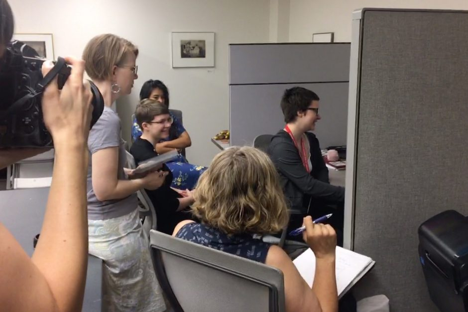 A photographer takes a picture of three students and two professors discussing a video playing on the computer monitor