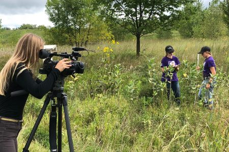 A photographer takes video of students working in the prairie