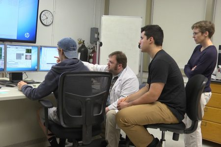 Students and Professor Walsh look at computer screen during research project