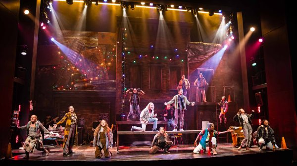 The cast of rent sings on stage