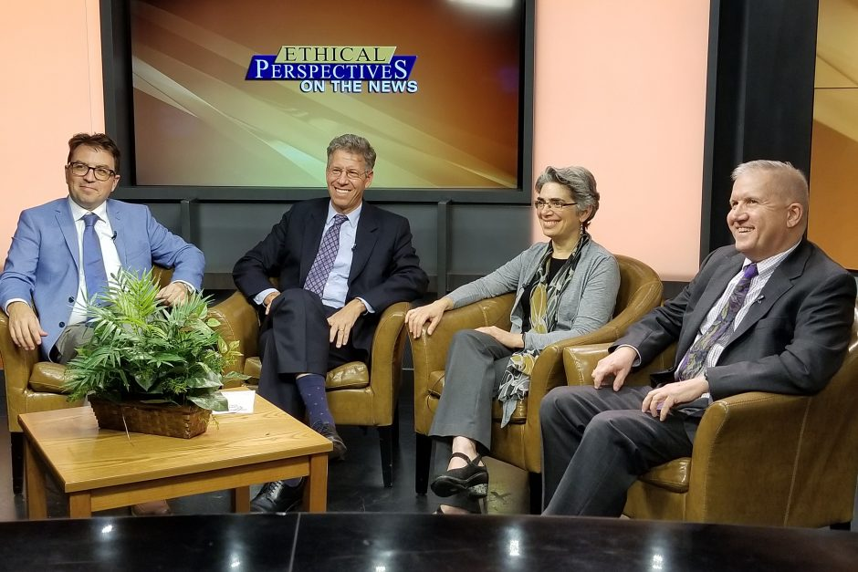 A panel of speakers smiles for a photo on the tv set
