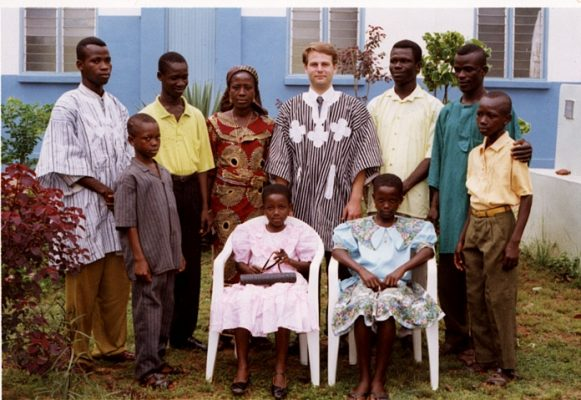 Craig Vickstrom '92 (center) still visits the family he lived with in Ghana. Members of the family are seen with him in front of their home; the seated girls are now bankers.