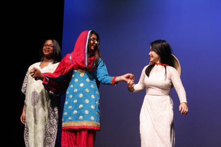 Three students perform on stage for the Culture Show at Cornell College