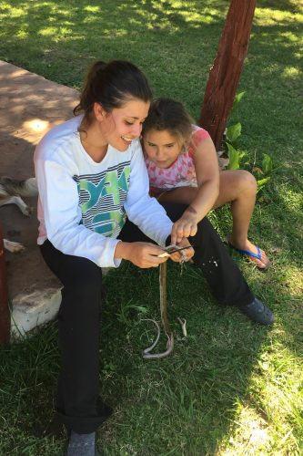 Maria Goodfellow '16 dissects a snake with a neighbor girl. The nonvenomous snake had been killed by the family, and she used it as a teachable moment.