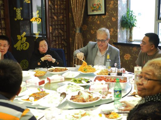 Professor Tony deLaubenfels shares a meal with hosts in China.
