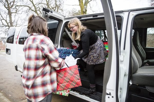 Students load packages into a van.