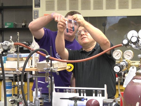 Charley Liberko and Ben Hewson look at test tubes