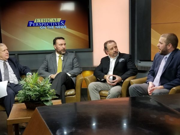 Four people talking on a television set