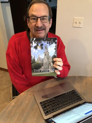 "Michael Bellito '72 holding his book ""The Hilltop (A College Tale)"""