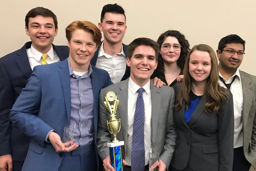 Cornell College Mock Trial Team holds a trophy and smiles for a photo