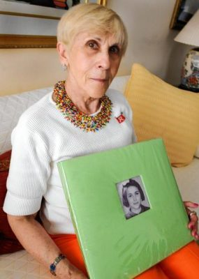 Rachel Goldman Miller holding a photo of a young child