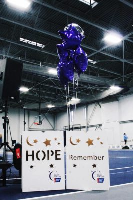 "Two signs saying ""hope"" and ""Remember"" with purple balloons for Relay for Life 2018"