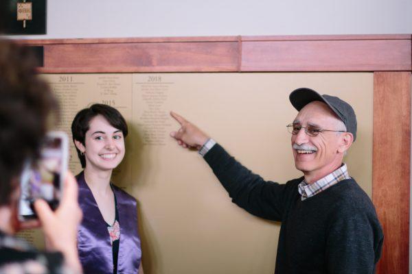 Family looks at name on Phi Beta Kappa plaque.
