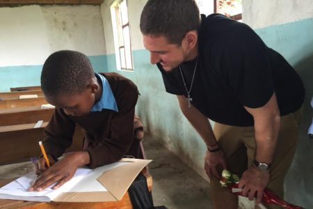 Futrell with a child during the Economic Development in Rural Tanzania class in 2016