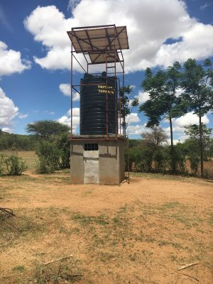Photo of a water system in Tanzania with a well and solar panels.