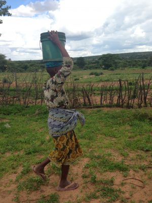 Woman walking with a bucket on her head in Africa.