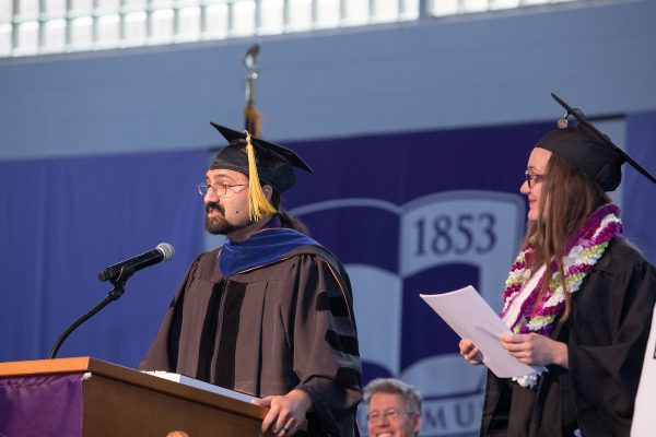 Associate Professor of Chemistry Jai Shanata and Belou Quimby '19 on stage during Commencement