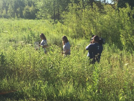Photographer taking video of students doing research in an Iowa prairie