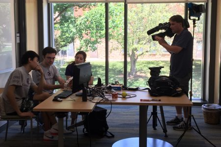 Videographer captures video of students and professor working on summer research