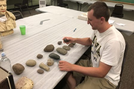 Caleb Blair sorts artifacts from a dig site.