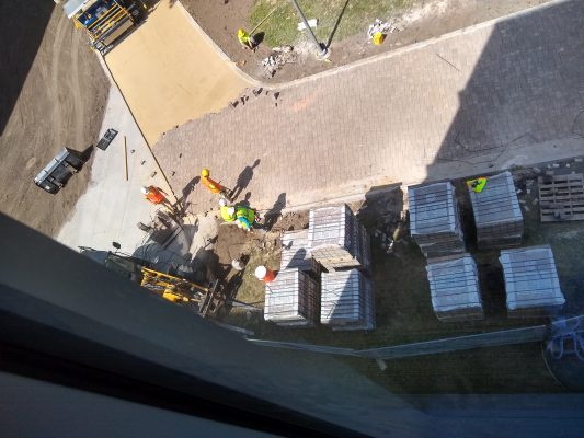 construction crews installing pavers on the new ped mall walking path
