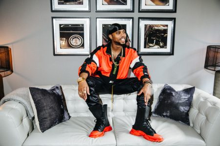 B.o.B sitting on a couch to promote Big Event